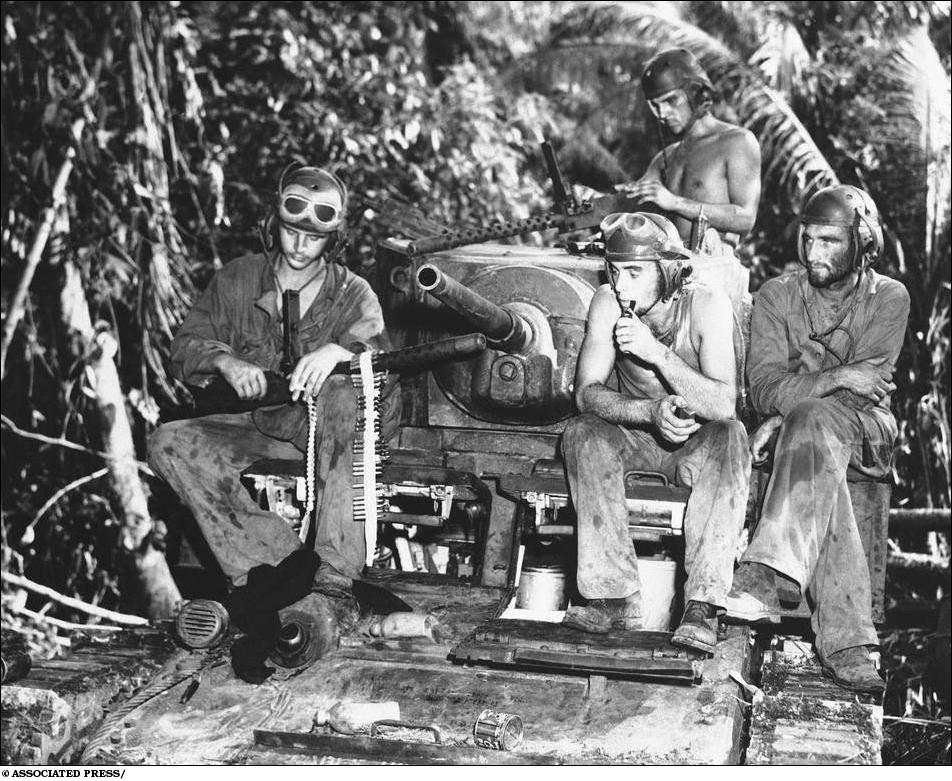 Sept. 11, 1943: After three days of fighting on the front lines on Munda, a Marine's tank crew take a rest, during which their machine guns are overhauled. This platoon wiped out 30 Japanese pill boxes. Left to right are: Pfc. Arnold McKenzie, Los Angeles, Calif.; Joseph Lodico, Sharon, Mass.; Pvt. Noel M. Billups, Columbus Ohio; and Staff Sgt. Douglas Ayres, Los Angeles. (AP Photo)