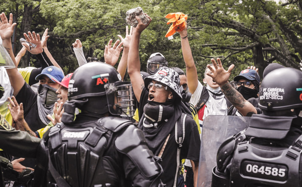 Толпа противостоит тяжелобронированному ESMAD (колумбийский ОМОН).
